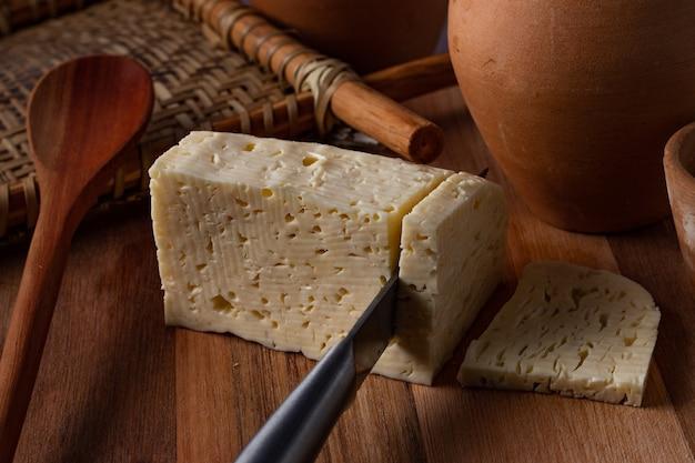 木製のテーブルでスライスされているレンネットチーズ