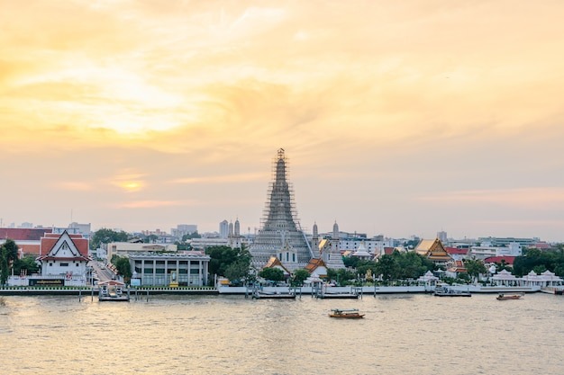 Renovated wat arun (the temple of dawn) with boats moving over chaophraya river in the evening in bangkok, thailand.