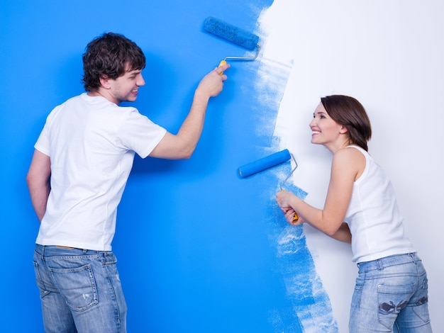 Renovation by laughing cheerful loving couple brushing the wall