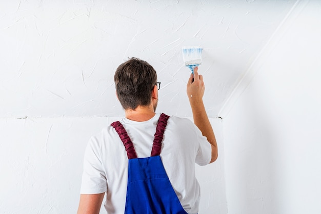 Renovation concept. man in blue suit overall painting wall with roller