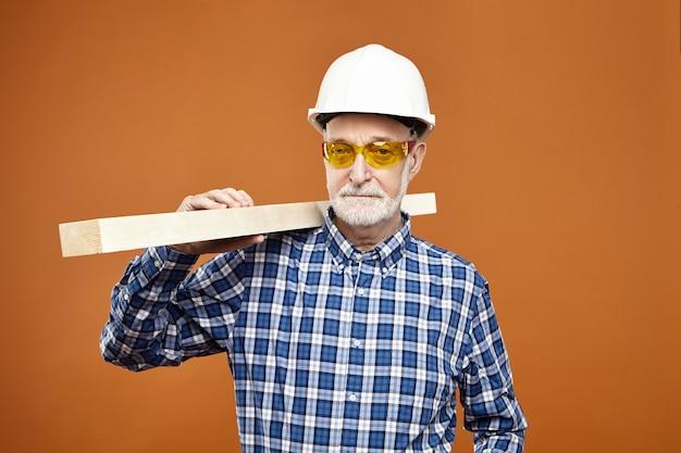 改修、建設、工芸。保護用のヘルメットと格子縞のシャツを着た真面目な年配のひげを生やした男性の水平方向のショット。肩に木の板を持ち、木を磨いて滑らかにする