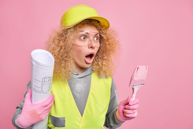 Renovation and construction concept. scared curly haired female builder holds blueprint and painting brush looks away with stupefied expression dressed in uniform
