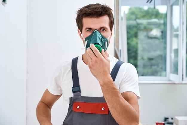 Renovation handyman puts on respirator.