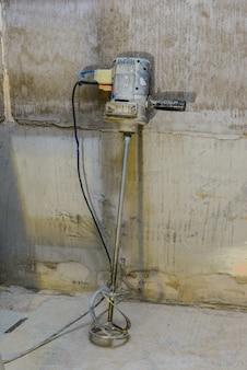 Евроремонт в ванной. смеситель для стройматериалов на стену из серого бетона.