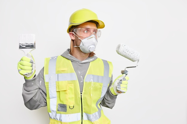 Renovation maintenance and engineering concept. busy male labourer focused into distance with worried expression wears protective helmet safety gloves holds roller and brush follows repairing steps