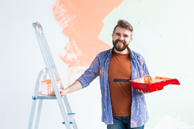 Renovation, redecoration and repair concept - cheerful guy painting wall in new home.