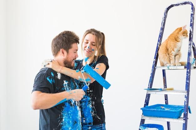 Ремонт ремонта и концепция семьи молодая пара с кошкой делают ремонт в новом доме