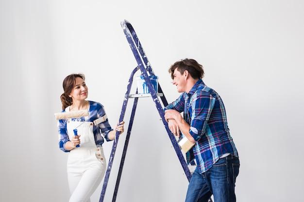 改装、修理、人々のコンセプト – 夫婦が壁に絵を描き、とても幸せそうに見える