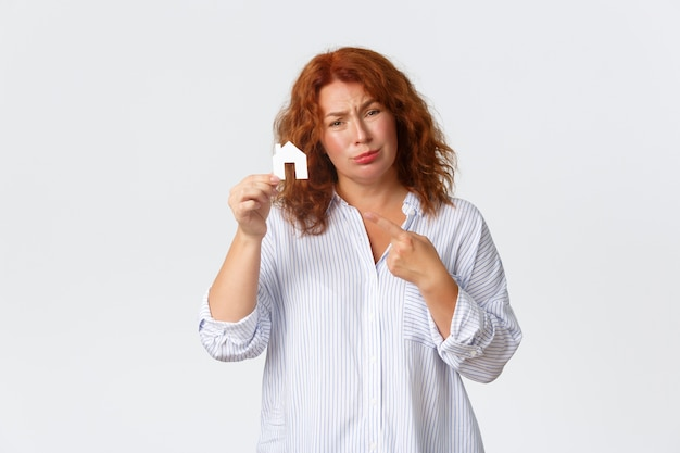 Rent, buying property and real estate concept. sad middle-aged redhead lady dreaming of having house, pointing at home cardboard and complaining not having money, need loan for buying.