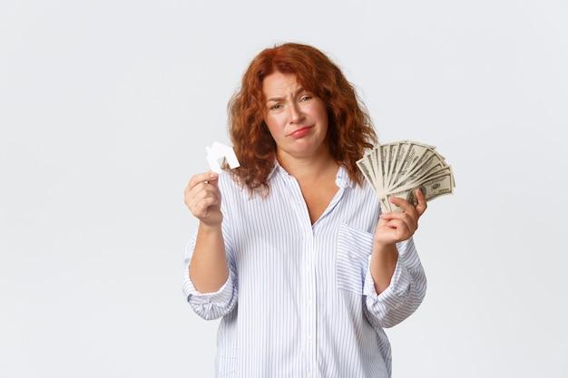 Affitto, acquisto di proprietà e concetto di bene immobile. donna di mezza età dai capelli rossi triste e divertita che tiene soldi e tessera piccola casa, non ha abbastanza soldi, ha bisogno di prestito per l'acquisto, muro bianco.