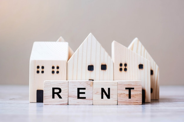 Rent cube blocks with wooden house model on table background. Premium Photo