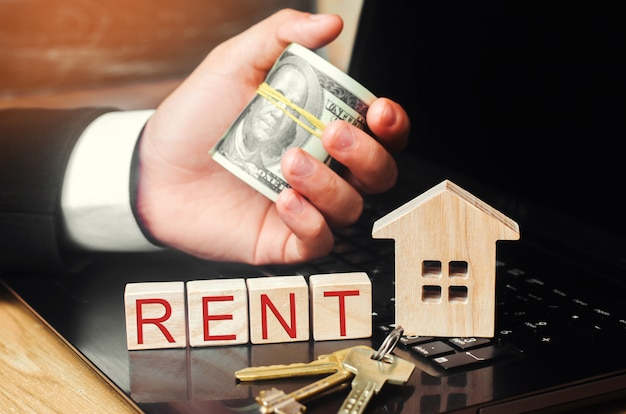 Rent a house online. concept of real estate. model of the house, keys, dollars