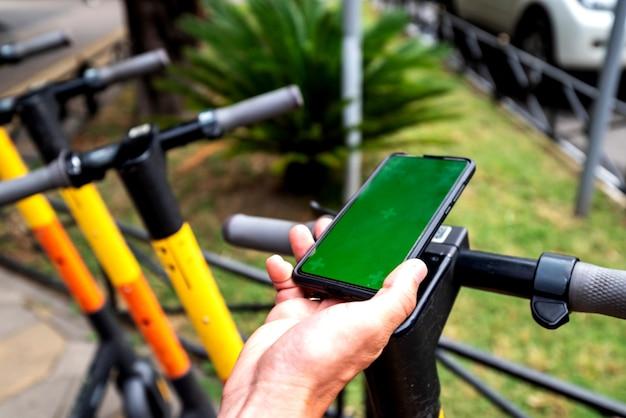 크로마 키 화면이있는 스마트 폰 전화를 기반으로 한 전기 스쿠터 임대, 비접촉식 지불. 젊은 남자는 여름에 친환경 교통수단을 빌린다. 전기 스쿠터 주차.
