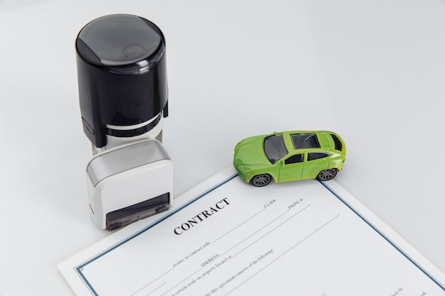 계약서, 우표 및 장난감 자동차가있는 자동차 임대 계약.