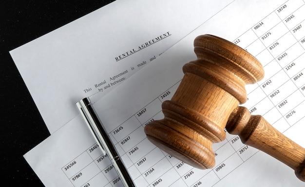 Форма договора аренды на рабочем столе с ручкой и молотком