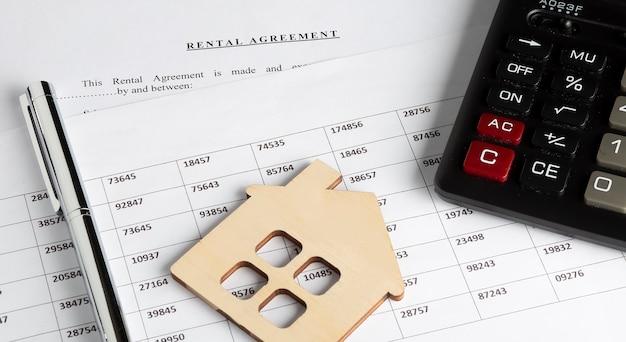 Форма договора аренды на рабочем столе с ручкой, макетом деревянного дома, таблицей и калькулятором