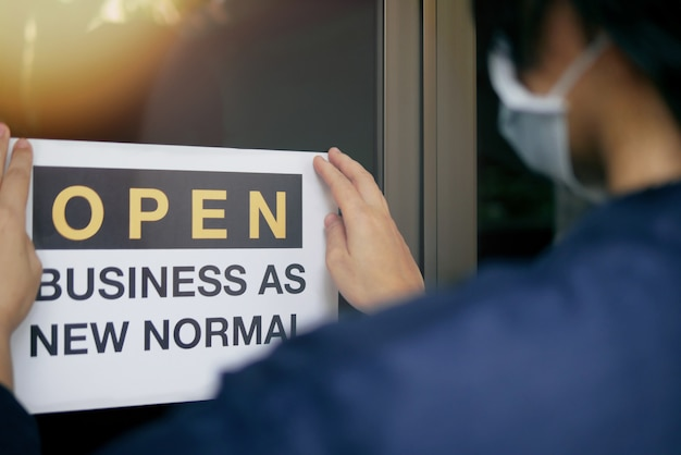 Reopening for business adapt to new normal in the novel coronavirus covid-19 pandemic. rear view of business owner wearing medical mask placing open sign open business as new normal on door.