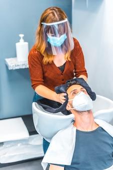 コロナウイルスの大流行後の美容院の再開。フェイスマスクと保護スクリーンを備えた美容師、covid-19。社会的距離、新しい正常性。お客様の髪を抜く