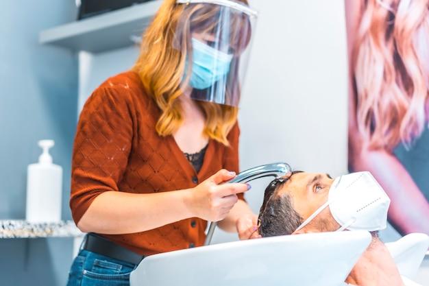 コロナウイルスの大流行後の美容院の再開。フェイスマスクと保護スクリーンを備えた美容師、covid-19。社会的距離、新しい正常性。お湯でクライアントの髪を洗う