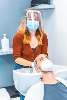 コロナウイルスの大流行後の美容院の再開。フェイスマスクと保護スクリーンを備えた美容師、covid-19。社会的距離、新しい正常性。石鹸でクライアントの髪を洗う