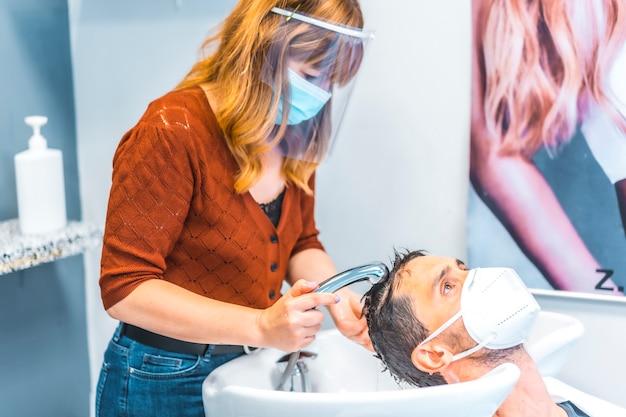 コロナウイルスの大流行後の美容院の再開。フェイスマスクと保護スクリーンを備えた美容師、covid-19。社会的距離、新しい正常性。クライアントの髪を洗う