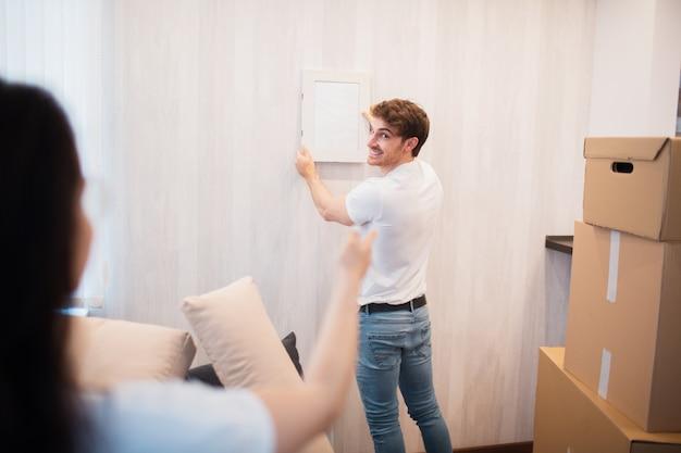 수리, 숙박 및 부동산 개념. 새 집으로 이사하고 벽에 그림이나 사진 프레임을 걸고 웃는 커플