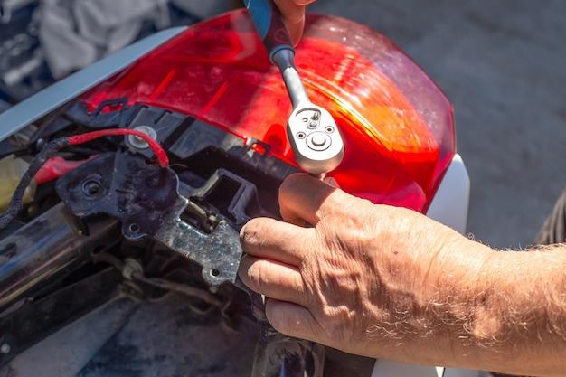 오토바이 수리 및 해체. 한 남자가 소켓 렌치로 트렁크 패스너의 나사를 풉니다.