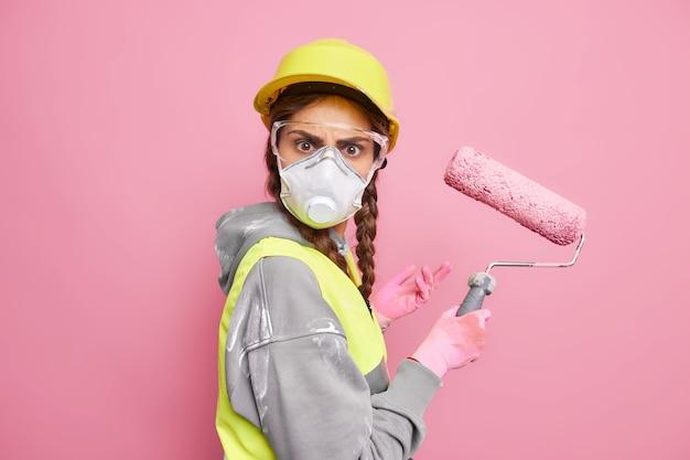 수리 및 유지 보수 서비스. 심각한 바쁜 여성 건축업자는 롤러로 집 페인트 월마트를 수리합니다.