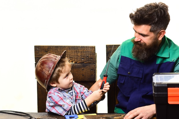 Repair bearded man with little assistance fatherhood concept son and father repairing together boy