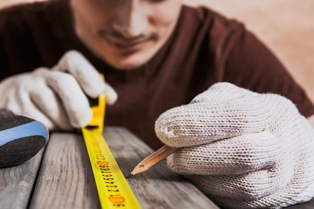수리, 건물 및 주택 개념 - 나무 판자를 측정하는 남성의 손을 클로즈업합니다. 전문 목수가 노란색 줄자와 연필로 정확한 측정을 합니다. 가구 도구.