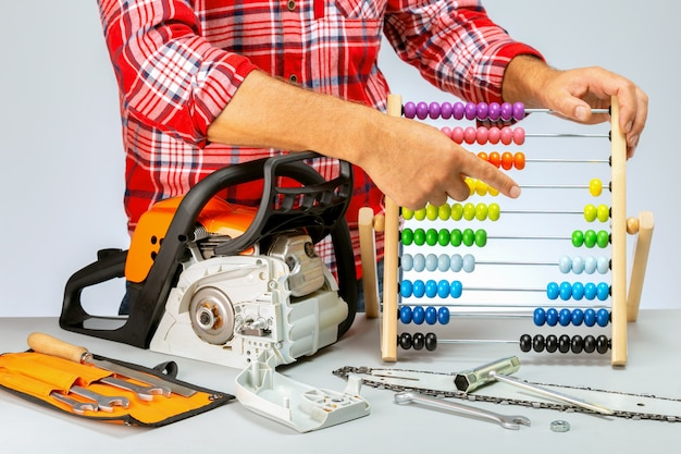 Repair of chainsaws,gasoline powered tools. repairman calculating the price.