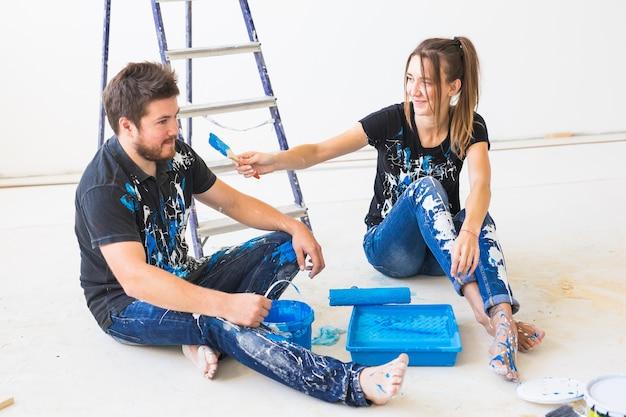 修理、色、人のコンセプト – 夫婦が壁を塗り、色を準備して楽しんでいる