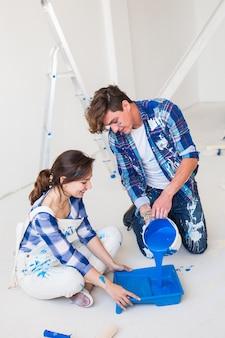 수리, 색상, 사람들 개념-부부는 벽을 칠할 것입니다. 그들은 색상을 준비하고 있습니다.