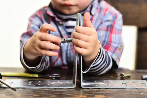 子供の手のボルトのクローズアップの概念で金属板の部品を接続する概念の子供の手を修理する