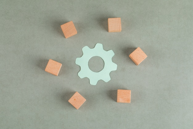 Repair concept with wooden cubes, settings symbol on grey table flat lay.
