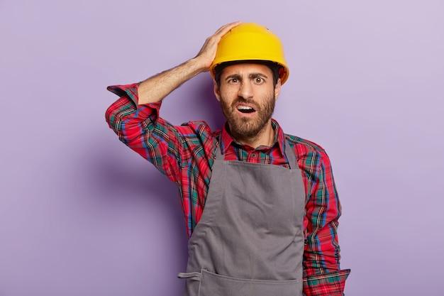 修理、建設、メンテナンスのコンセプト。不満を持った無精ひげを生やした便利屋は、黄色の保護用ヘッドギア、エプロン、シャツを着て、手作業をします。ネガティブな表情の建設作業員