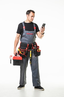 Repair, construction and building. male worker or builder with smartphone and working tools on belt and box