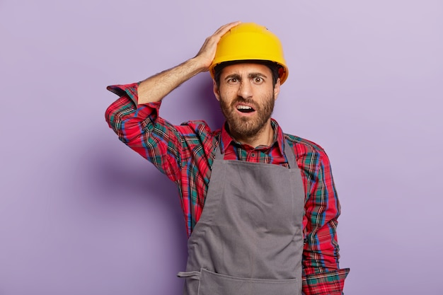 Repair, construction and maintenance concept. dissatisfied unshaven handyman wears yellow protective headgear, apron, shirt, does manual work. construction worker with negative face expression