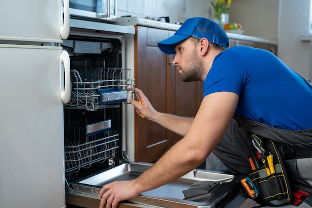 Repair of dishwashers repairman repairing dishwasher in kitchen