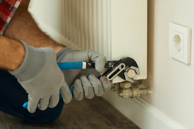 Ремонт отопления крупным планом снимок мужских рук с разводным гаечным ключом, разнорабочий ремонтирует отопление
