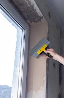 아파트 수리, 창 개구부 접착, 남자 건축업자가 퍼티 나이프로 퍼티를 수평으로 맞추다