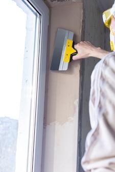 Ремонт в квартире, заделка оконных проемов, мужчина строитель выравнивает шпаклевку шпателем.