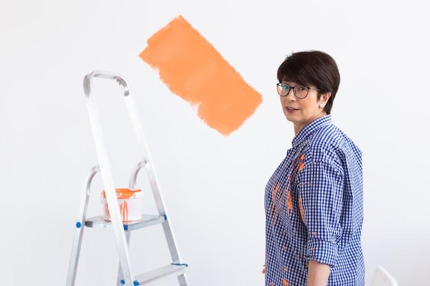 아파트 수리. 행복 한 중 년 여자는 페인트로 벽을 그립니다.