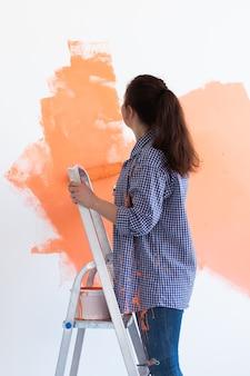 아파트 수리. 행복 한 여자는 페인트로 벽을 그립니다.