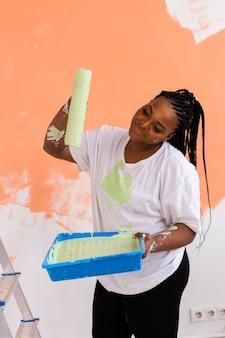 Ремонт в квартире. счастливая молодая женщина красит стену краской.