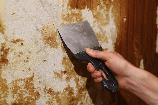 へらで古い壁紙をはがすアパートの修理