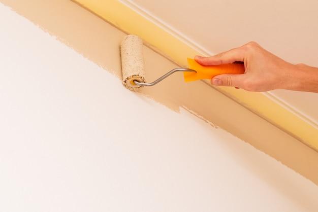 Ремонт в доме. мужчина красит стены комнаты валиком в бежевый цвет. концепция с копией пространства