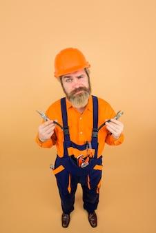 修理業界のビルダーの男真面目な労働者は、建設中のビルダーを構築する修理ツールを保持しています