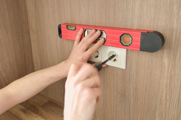 Repair and installation of furniture, hands of electrician worker installing electrical outlet in furniture using screwdriver and level