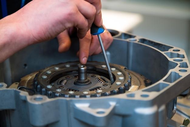 Ремонтник, фиксирующий автомобильную часть с помощью отвертки.